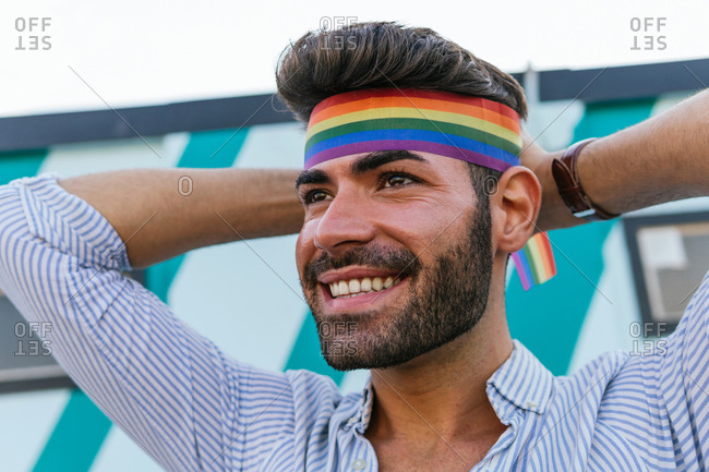 Low angle of homosexual male putting on bright headband in colors of rainbow LGBT flag while standing in city and looking away with smile