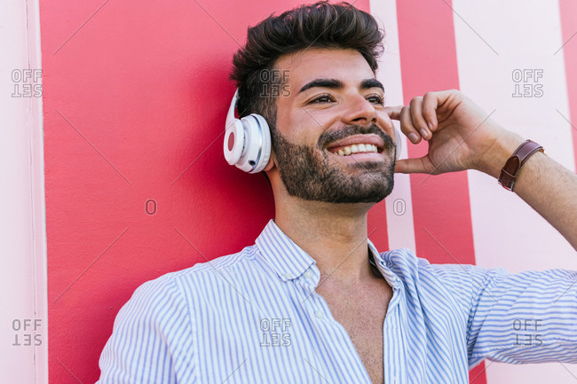 Carefree gay male with LGBT bracelet and in headphones standing on street on colorful wall while enjoying songs and looking away