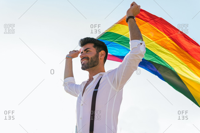 Low angle of expressive homosexual male standing on street with bright rainbow flag and cheerfully screaming