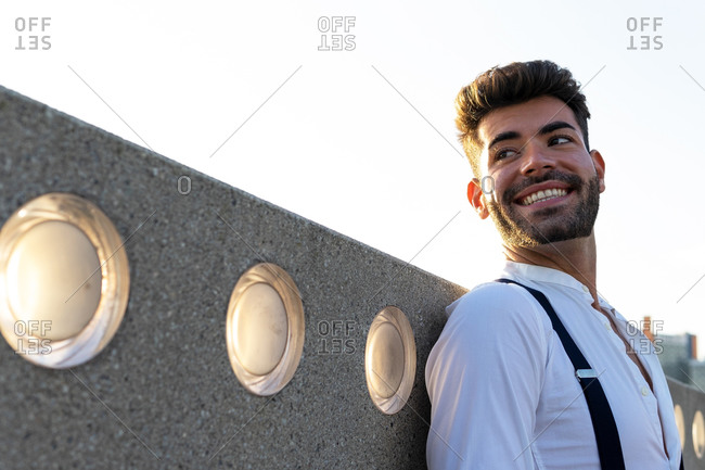 Low angle of masculine male with toothy smile and in stylish clothes standing on street at sundown and looking away