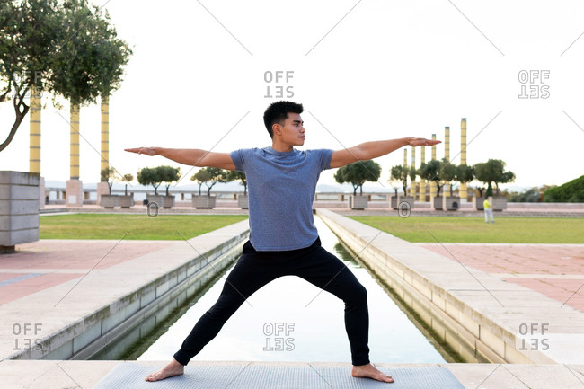 Side view of flexible Asian male in sportswear practicing yoga in Virabhadrasana with raised arms while standing barefoot on mat in city
