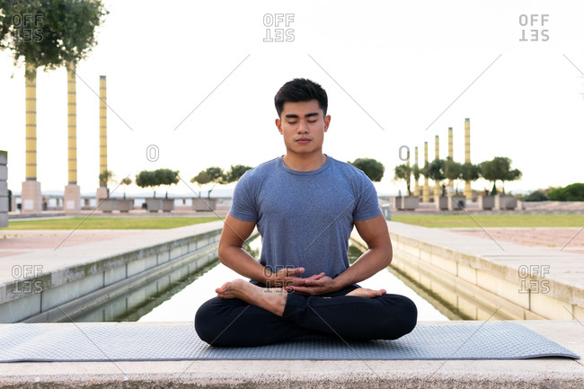 Flexible Asian male sitting on mat in Padmasana and meditating with closed eyes while practicing yoga in park