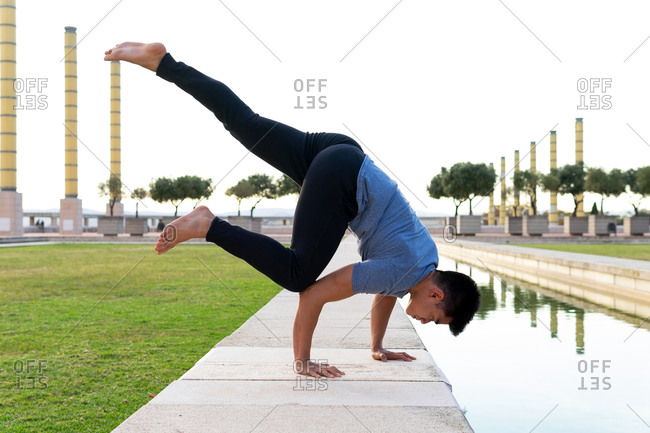 Side view of fit Asian male balancing on arms in Eka Pada Kakasana while practicing yoga in park near pond