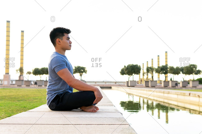 Side view flexible Asian male sitting on mat in Padmasana and meditating with closed eyes while practicing yoga in park