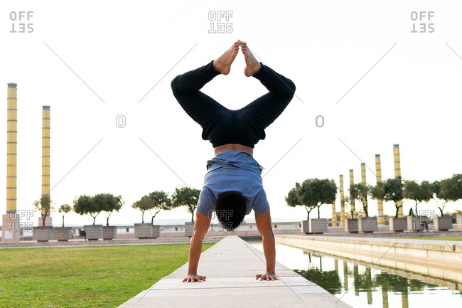Upside down view of unrecognizable male balancing on hands in Adho Mukha Vrksasana while doing yoga on mat in park