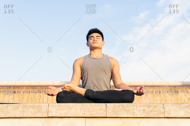 Tranquil focused Asian male in activewear in lotus pose meditating near fountain in city with eyes closed