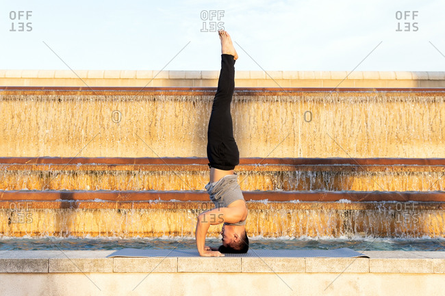 Side view of slim male standing in Supported Headstand pose on mat and practicing yoga near fountain in city on sunny day
