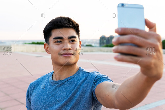 Handsome Asian male standing in city while taking photo on selfie camera of cellphone and smiling