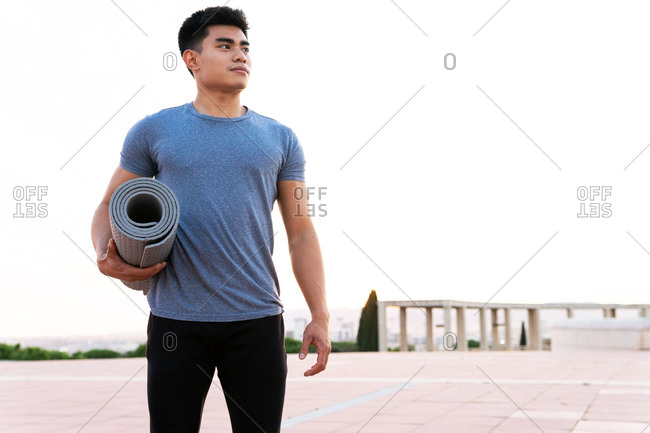 Content Asian male in sportswear standing with twisted yoga mat on street and looking away