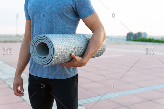Cropped unrecognizable male in sportswear standing with twisted yoga mat on street and looking away