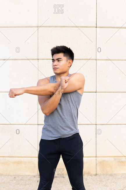 Confident athletic Asian male in sportswear standing on street and stretching arms before active training while looking away