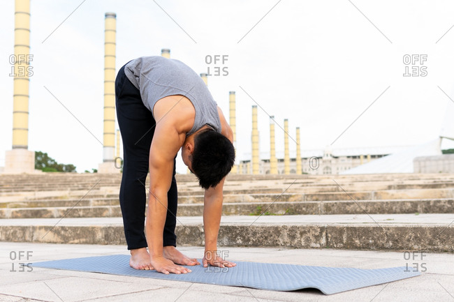 Tranquil unrecognizable male barefoot on mat and stretching body while on downward facing dog pose doing yoga in city