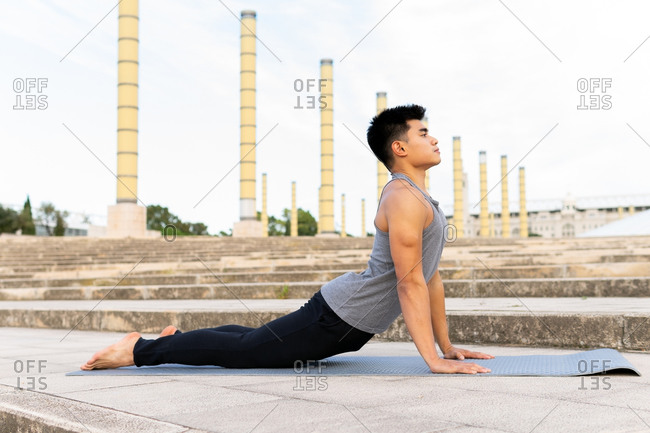 Side view of flexible focused Asian male practicing yoga on mat in Bhujangasana while stretching back and looking away