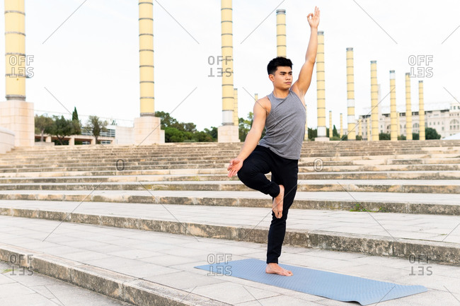 Young concentrated Asian male standing in Vrksasana with mudra gesture and doing yoga on mat on stairs in city park