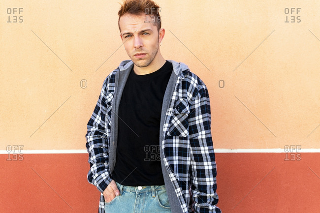 Confident young hipster guy in casual checkered shirt looking at camera and smiling while standing against orange wall