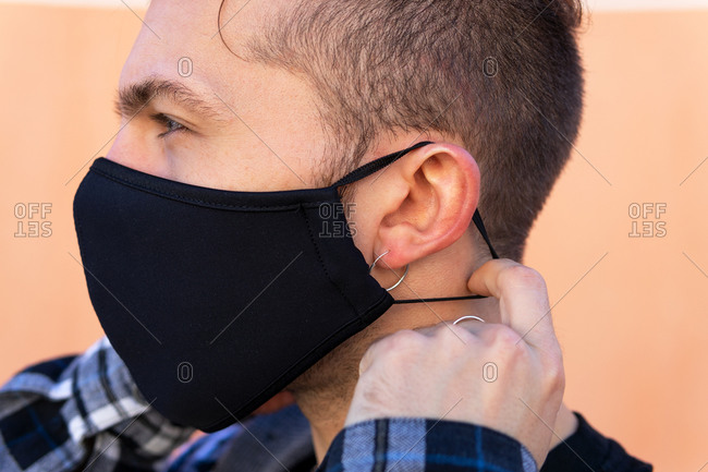 Side view of modern hipster male with piercing putting on black protective mask for coronavirus prevention against beige background