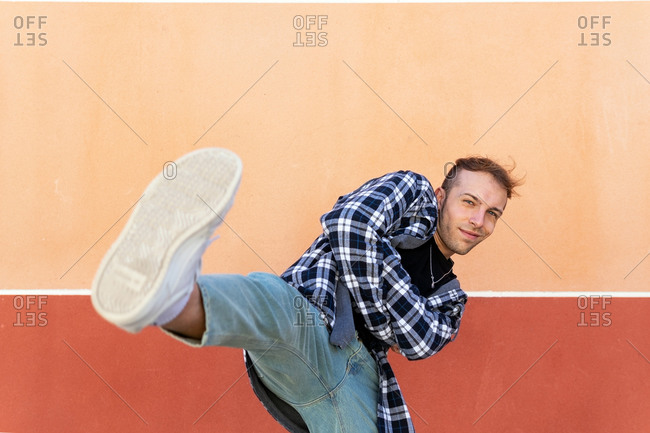 Smiling young hipster guy in casual checkered shirt and jeans performing kick and looking at camera against colorful wall