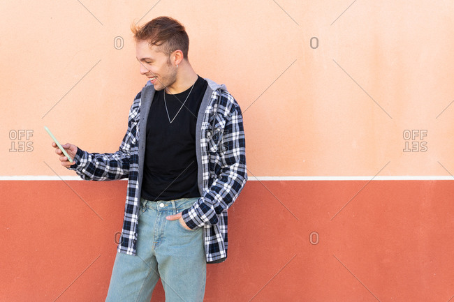Content young male in casual checkered shirt and jeans messaging on mobile phone while standing against colorful wall