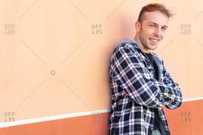 Side view of positive confident young hipster guy in casual checkered shirt looking at camera and smiling while standing against orange wall