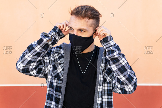 Modern hipster male putting on black protective mask for coronavirus prevention against beige background looking away