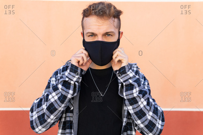 Modern hipster male putting on black protective mask for coronavirus prevention against beige background looking at camera
