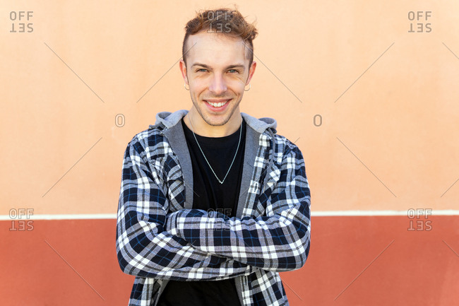 Positive confident young hipster guy in casual checkered shirt looking at camera and smiling while standing against orange wall