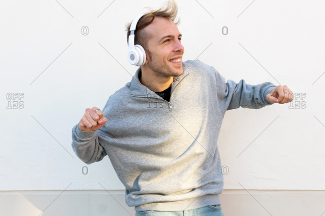 Cheerful young male in casual outfit and sneakers listening to music through headphones and dancing near stone wall on street