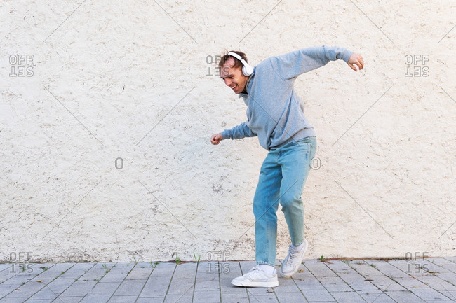Full body of cheerful young male in casual outfit and sneakers listening to music through headphones and dancing near stone wall on street