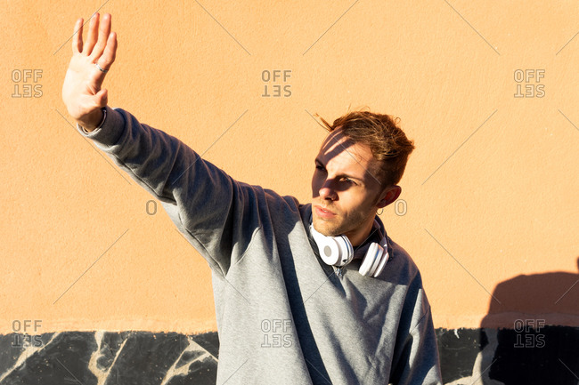Modern unshaven hipster male in casual sweatshirt with headphones on neck outstretching arm and covering face from bright sunshine while standing against yellow stone wall on street