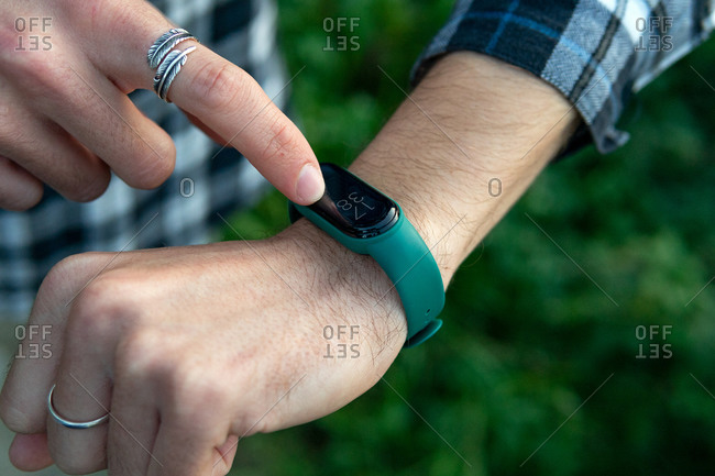 Closeup of crop anonymous male in casual checkered shirt touching smart watch and checking notifications