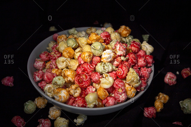 Tasty colorful popcorn in bowl placed on black background in studio