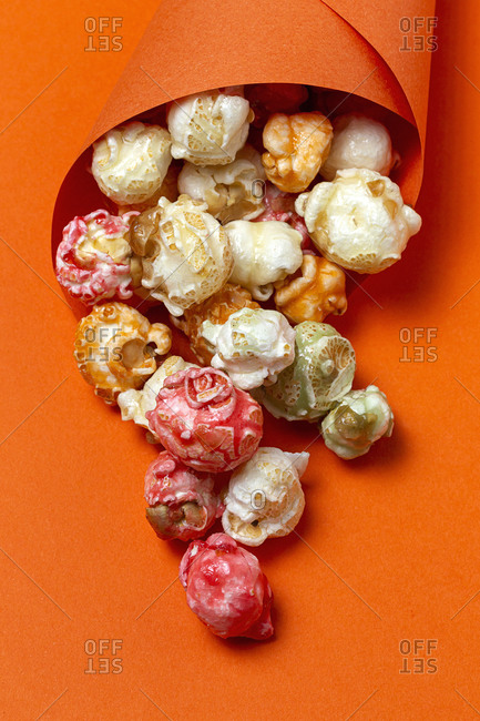 High angle of colorful tasty popcorn in paper cone placed on orange background in studio