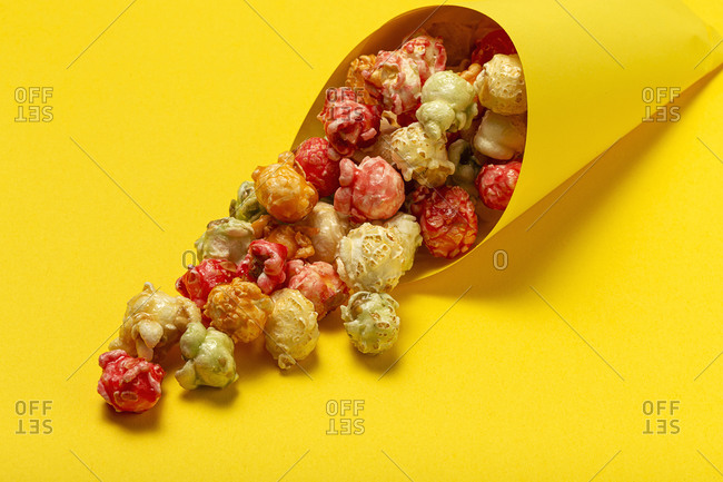 High angle of colorful tasty popcorn in paper cone placed on yellow background in studio