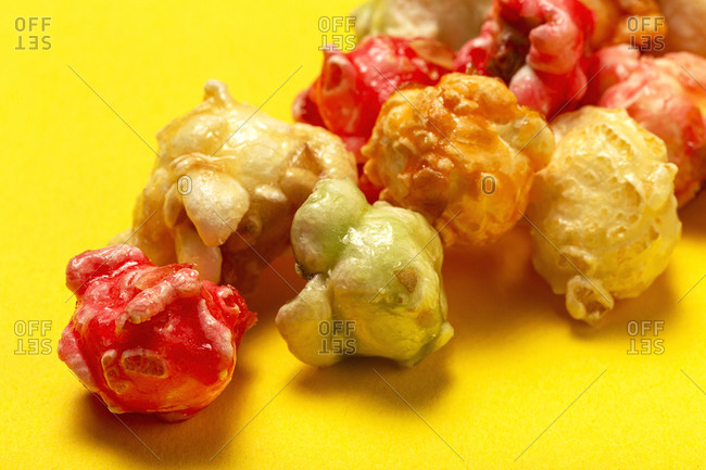 From above closeup of sweet colorful popcorn scattered on yellow background in studio