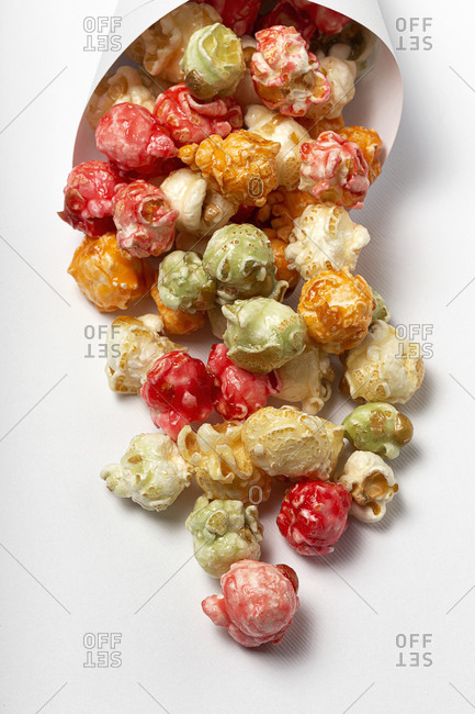 High angle of colorful tasty popcorn in paper cone placed on white background in studio