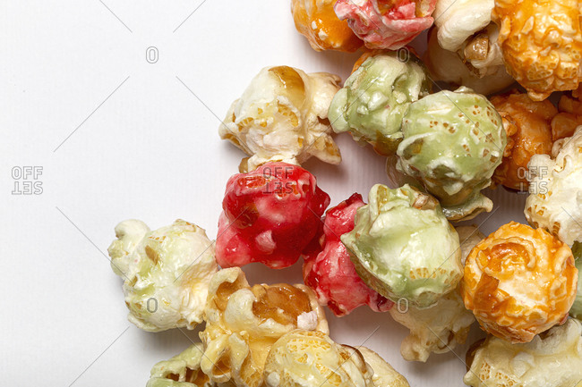 From above closeup of sweet colorful popcorn scattered on white background in studio