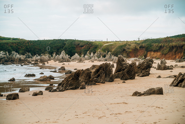 Scenery of seashore with rough rocks located in highland area on overcast day