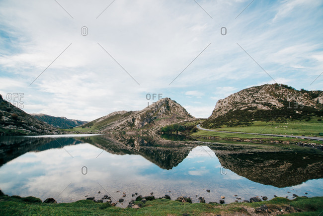 Rocky mountains and blue cloudy sky reflecting in smooth surface of calm pond in highland area