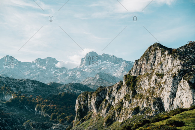 Wonderful scenery of rocky mountain ranges covered with green plants under blue sky on sunny day