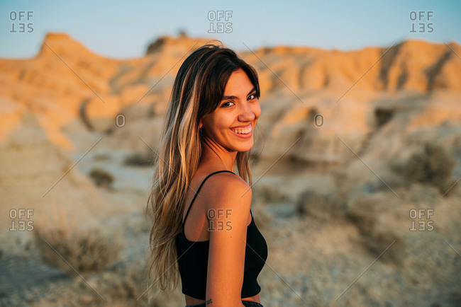 Positive female traveler standing in dry valley in Bardenas Reales and enjoying sunset in summer while looking at camera