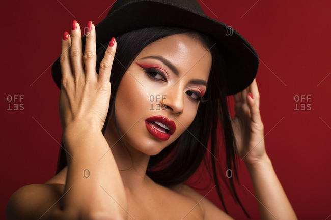 Magnificent female with red lips and in black hat standing with opened mouth and looking away on red background in studio