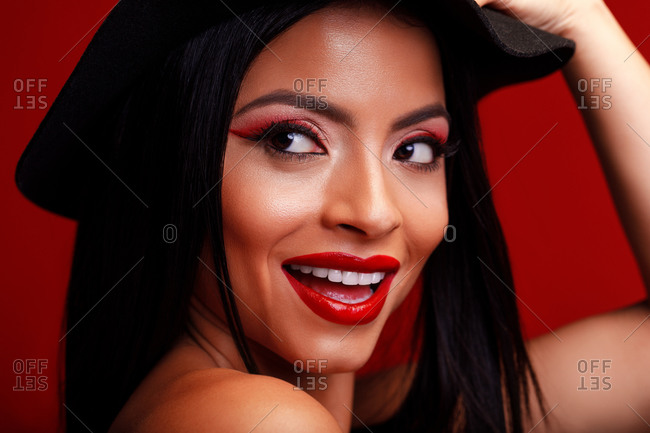 Cheerful female with red lips and in black hat standing on red background and smiling charmingly while touching head and looking away