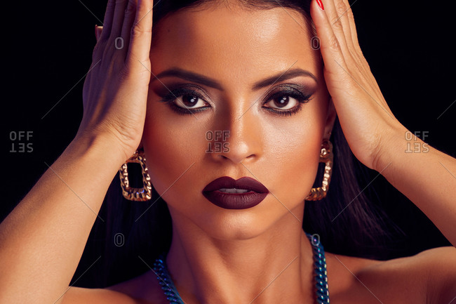 Attractive female with professional makeup and in trendy accessories touching head while standing with closed eyes on black background