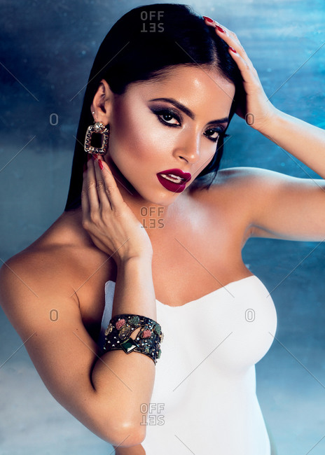 Curvy young female with red lips and body painted in white color standings in studio and looking at camera