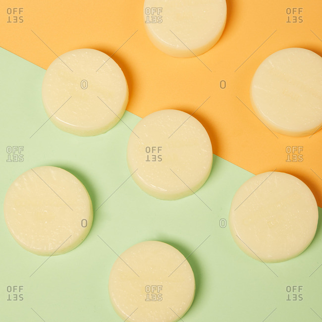 From above of natural round shaped soap arranged on two colored background in studio