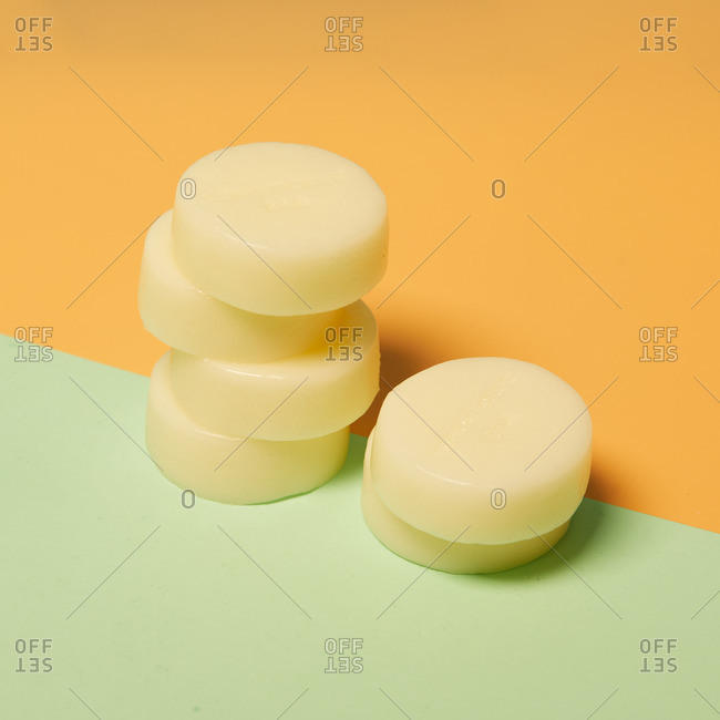 Natural round shaped soap arranged on two colored background in studio
