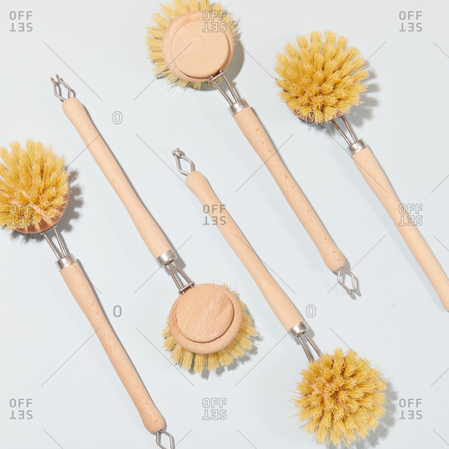 Top view of collection of eco friendly brushes for washing dishes arranged on white background in studio