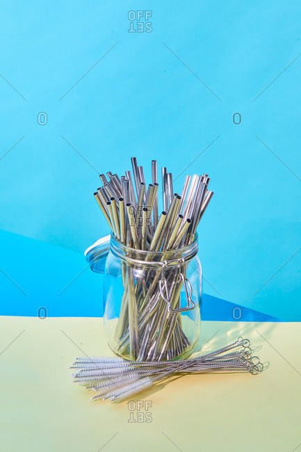 From above of many metal reusable straws placed in glass jar on table with cleaning brushes on blue background in studio