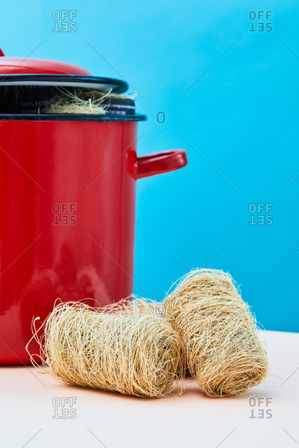 Natural eco friendly loofah sponges for washing dishes placed on table near saucepan in studio on vivid blue background