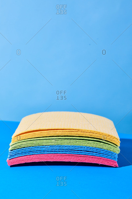 Closeup of heap of multicolored rags placed on blue background in studio demonstrating concept of cleaning and housework